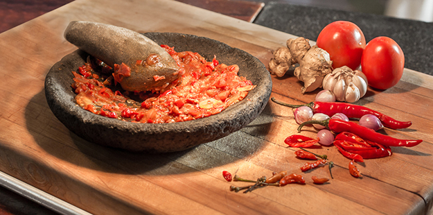The traditional method for preparing sambal involves crushing the ingredients with a stone mortal and pestle. Photo by Marco Fierli